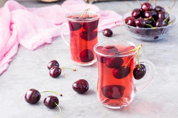 Compote froide sucrée à base de cerises fraîches dans une tasse en verre