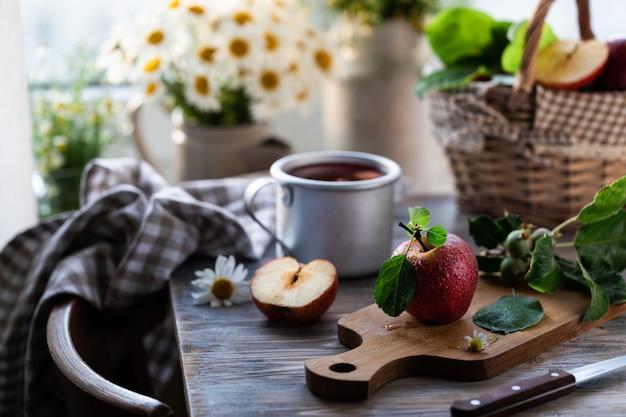 Compote de pommes d'été sur une table en bois près de la fenêtre avec de la camomille sauvage dans le pot