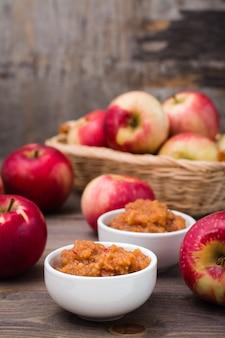 Compote de pommes fraîche dans des bols et des pommes rouges sur une table en bois.