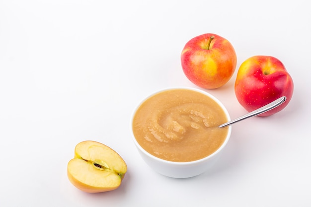 Compote de pommes maison fraîche. le concept d'une bonne nutrition et d'une alimentation saine. nourriture biologique et végétarienne. bol blanc avec purée de fruits sur tissu et pommes coupées sur table. nourriture pour bébés