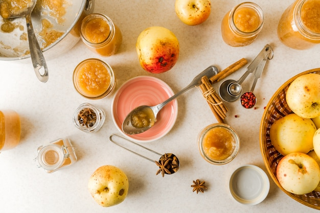 Compote de pommes maison fraîche dans des bocaux en verre, assiette, ustensiles, ingrédients sur la table de la cuisine