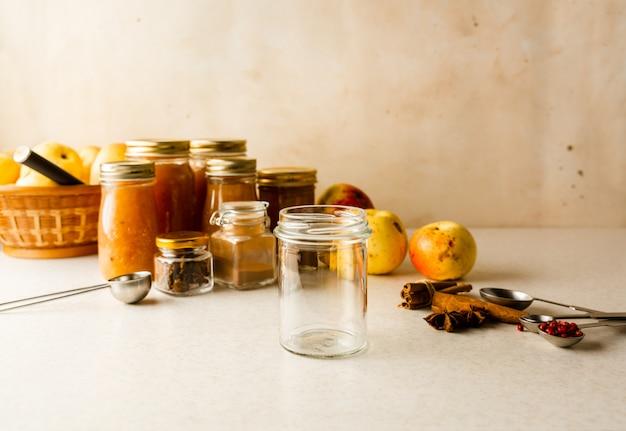 Compote de pommes maison fraîche dans des bocaux en verre, ingrédients sur la table de la cuisine