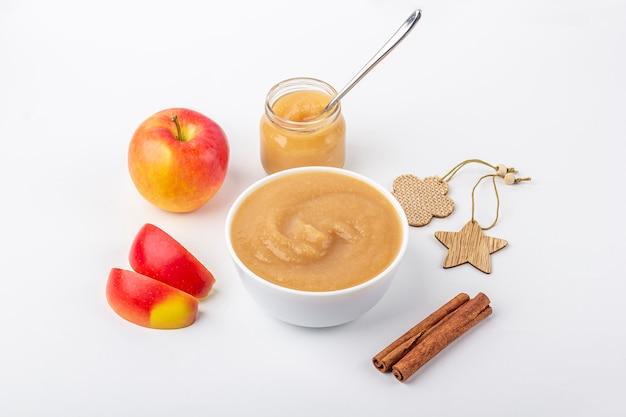 Compote de pommes maison fraîche dans un bol blanc et un pot avec de la purée de fruits sur le tableau blanc. le concept d'une bonne nutrition et d'une alimentation saine. nourriture biologique et végétarienne. nourriture pour bébés. copiez l'espace pour le texte