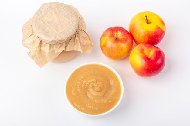 Compote de pommes maison fraîche dans un bol blanc et un pot avec de la purée de fruits sur le tableau blanc. le concept d'une bonne nutrition et d'une alimentation saine. nourriture biologique et végétarienne. nourriture pour bébés