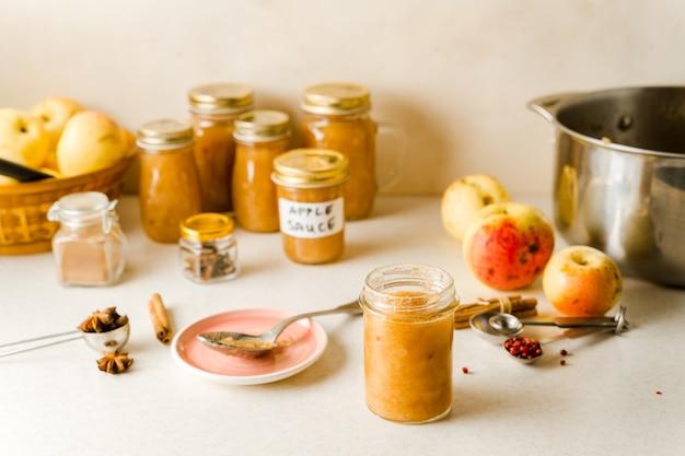Compote de pommes maison fraîchement préparée dans des bocaux en verre, ingrédients, assiette et cuillère sur la table de la cuisine
