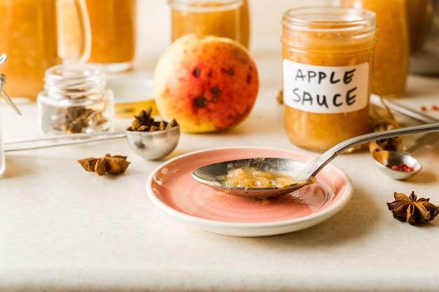 Compote de pommes maison fraîchement préparée dans des bocaux en verre, ingrédients, assiette rose et cuillère sur la table de la cuisine, vue rapprochée