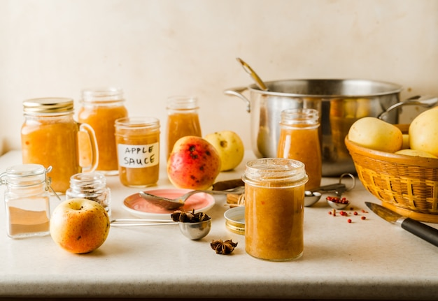 Compote de pommes maison fraîchement préparée dans des bocaux en verre, ingrédients, assiette, ustensiles sur la table de la cuisine