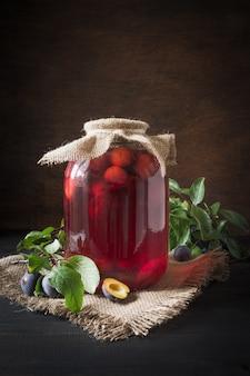 Compote de prunes en conserve faite maison dans de grands pots sur une planche de bois. style rustique.