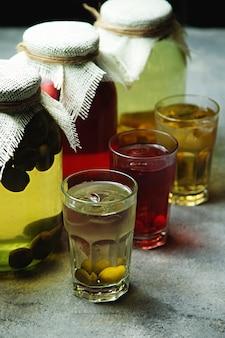 Compotes de fruits dans des bocaux en verre et des verres avec feijoa et cerise