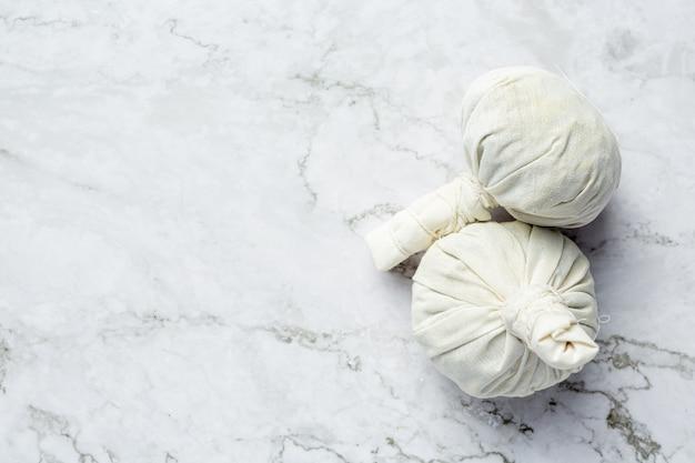 Compresse aux herbes posée sur un sol en marbre blanc