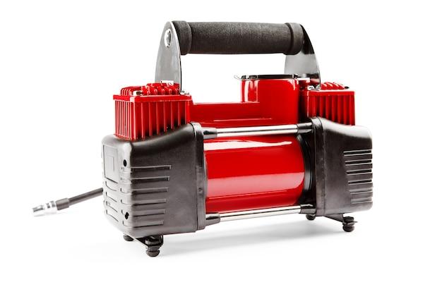 Compresseur de voiture isolé sur fond blanc. une pompe électrique gonfle une roue de voiture
