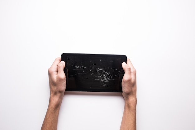 Comprimé cassé noir sur fond blanc. écran de gadget fissuré. le gars tient une tablette cassée dans sa main.