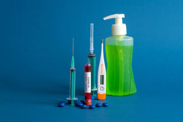 Comprimé de médicament, thermomètre, bouteille de désinfectant et seringue ou injection avec un tube à essai contenant un échantillon de sang pour tester la présence de coronavirus