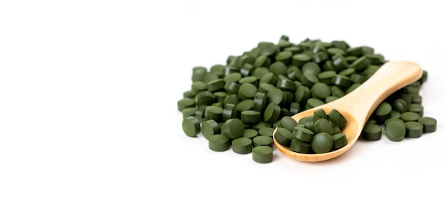 Comprimés d'algues spiruline avec cuillère isolé concept de santé de vitamines de suppléments nutritionnels