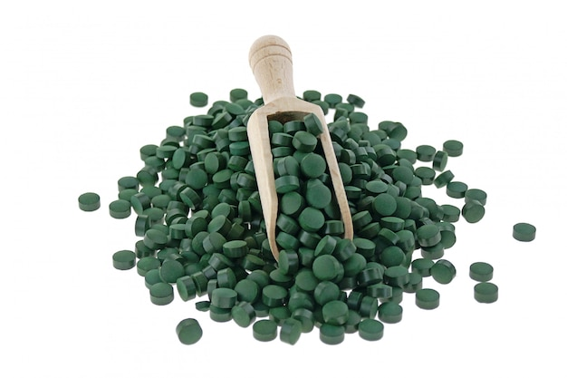 Comprimés d'algues spiruline dans un scoop isolé. concept de super nourriture. compléments alimentaires pour un mode de vie sain