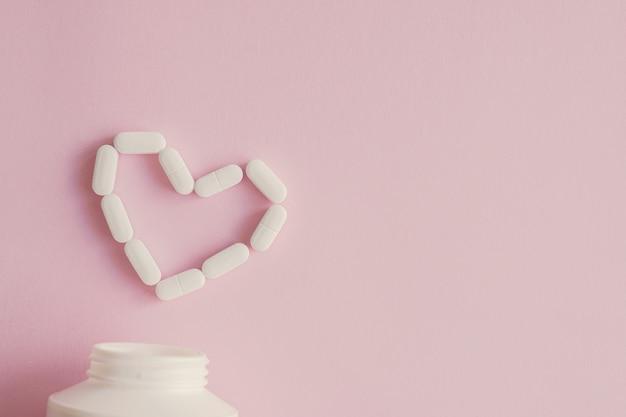 Comprimés blancs et pilules en forme de coeur pour les maladies cardiaques