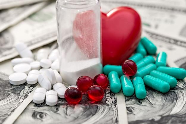 Des comprimés blancs, rouges et verts sont éparpillés sur les dollars et le cœur.
