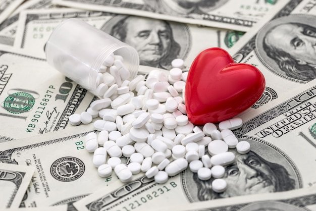 Les comprimés blancs sont éparpillés sur les dollars et le cœur.