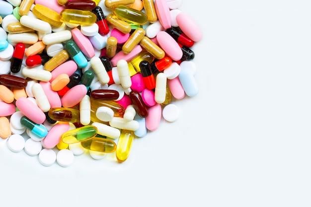 Comprimés colorés avec des capsules et des pilules sur blanc
