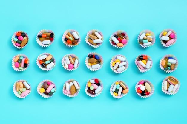 Comprimés colorés avec des capsules et des pilules dans des emballages de cupcakes sur fond bleu.