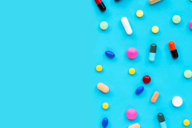 Comprimés colorés avec des capsules et des pilules sur fond bleu.