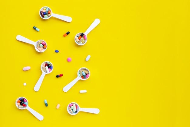 Comprimés colorés avec des capsules et des pilules sur jaune