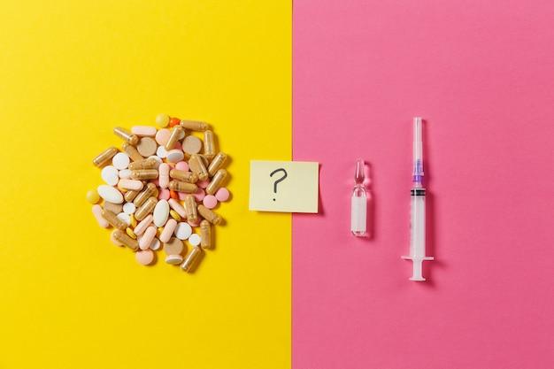 Comprimés colorés de médicaments, pilules arrangées abstraites sur fond rose jaune