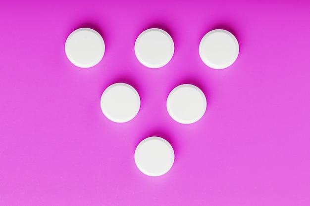 Comprimés d'ecstasy ronds en forme de triangle sur une surface rose