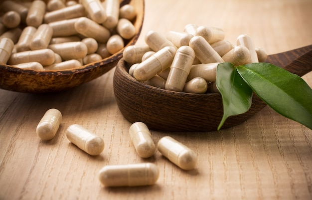 Comprimés de médecine alternative sur une cuillère en bois, feuille verte.