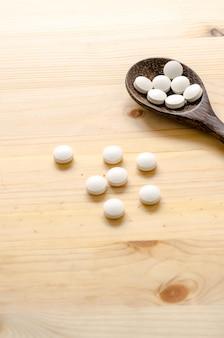 Comprimés de médecine et cuillère en bois sur fond de bois