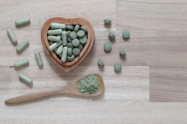 Comprimés de médecine d'extrait de fines herbes pilules avec capsules et poudre ou fa thalai chon (andrographis paniculata), acanthaceae dans un bol en bois sur fond de bois, concept médical et de soins de santé