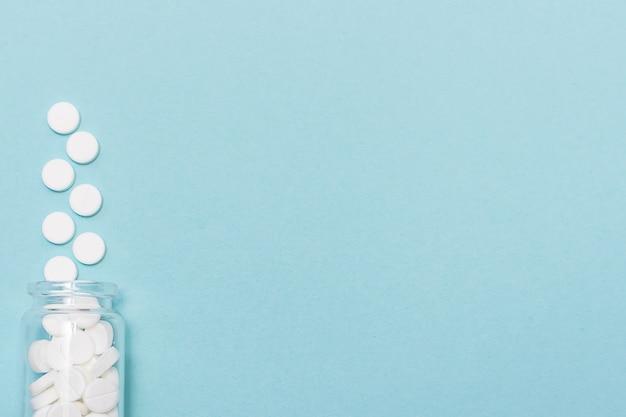 Comprimés médicaux blancs en bouteille en verre sur bleu, gros plan.