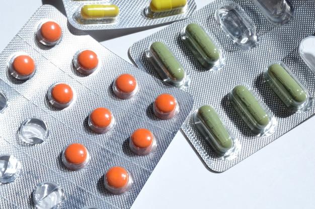 Des comprimés multicolores dans des blisters en aluminium se trouvent. fermer.