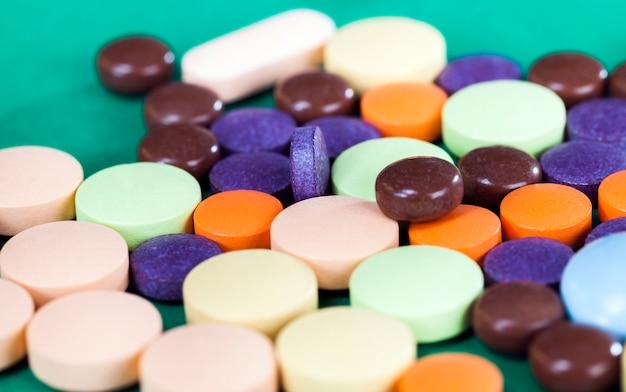 Comprimés multicolores sur fond vert