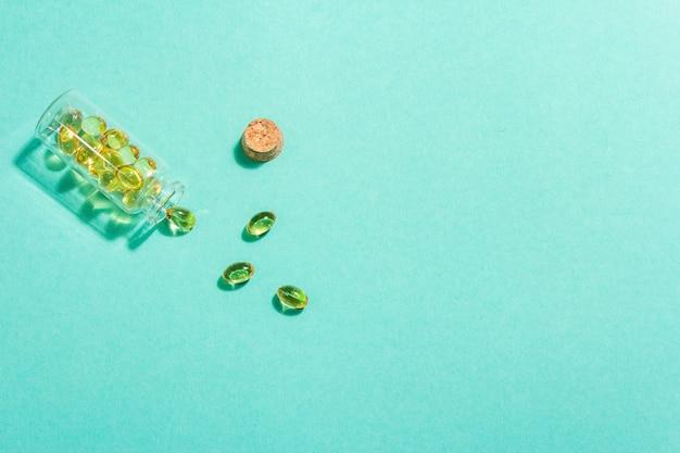 Comprimés omega3 dans un vieux flacon sur un mat turquoise.