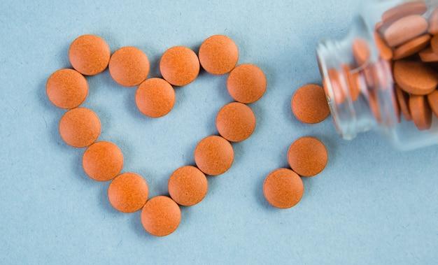 Les comprimés orange sont disposés en forme de cœur