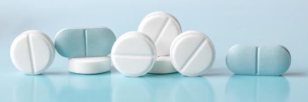 Comprimés et pilules blancs et bleus sur une lumière