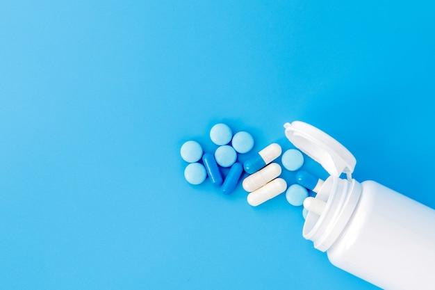 Comprimés de pilules de médecine pharmaceutique comprimés et capsules et bouteille sur fond bleu