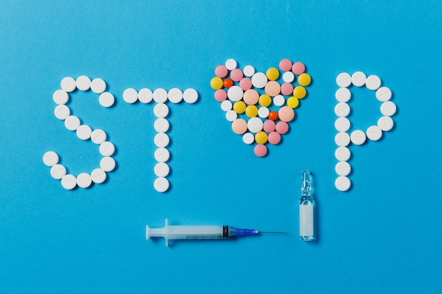 Comprimés ronds blancs et colorés de médicament dans le mot stop isolé sur fond bleu. coeur de pilules, ampoule, aiguille de seringue vide. concept de choix de traitement, mode de vie sain. copiez la publicité de l'espace.