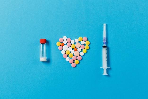 Comprimés ronds blancs et colorés de médicament sous forme de coeur d'isolement sur le fond bleu
