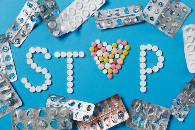 Comprimés ronds blancs et colorés de médicaments dans le mot stop isolé sur fond bleu