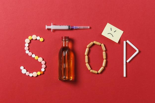 Comprimés ronds blancs de médicament dans le mot stop
