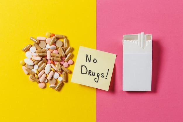 Les comprimés ronds colorés blancs de médicament ont arrangé des cigarettes abstraites de paquet sur le fond de couleur jaune