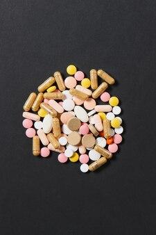 Les comprimés ronds colorés blancs de médicament ont arrangé le résumé sur le fond de couleur rouge