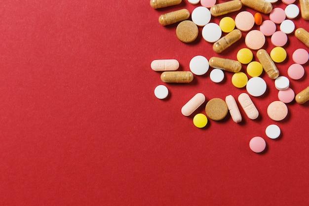 Les Comprimés Ronds Colorés Blancs De Médicament Ont Arrangé Le Résumé Sur Le Fond De Couleur Rouge Photo gratuit