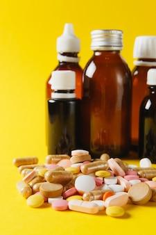 Comprimés ronds colorés blancs de médicaments disposés abstrait sur fond de couleur jaune. pilules de capsule de fiole de bouteille pour la conception. choix de traitement de santé concept de mode de vie sain. copiez la publicité de l'espace.