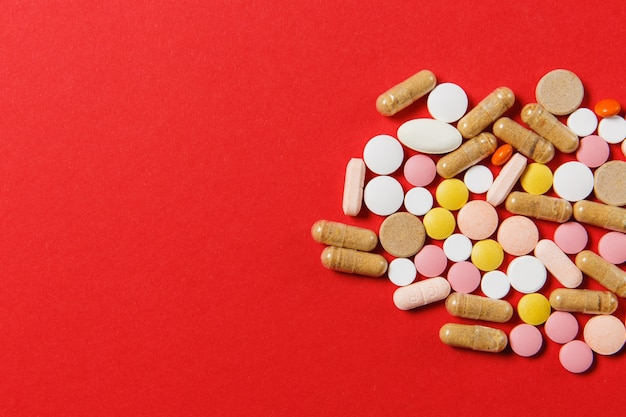 Comprimés ronds colorés blancs de médicaments disposés abstrait sur fond de couleur rouge. aspirine, gélules pour le design. santé, traitement, concept de mode de vie sain de choix. copiez la publicité de l'espace.
