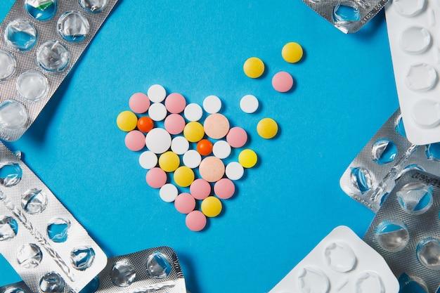 Comprimés ronds colorés de médicament sous forme de coeur de diffusion d'isolement sur le fond bleu