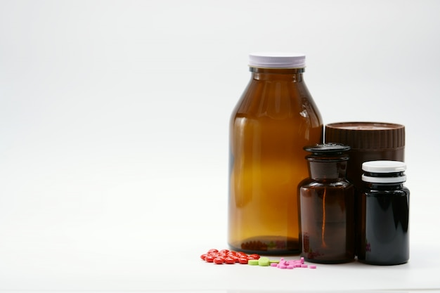Comprimés roses, verts et rouges sur fond blanc avec récipient de bouteille de médicament ambre. emballage résistant à la lumière. industrie pharmaceutique. produit de vitamines et suppléments. pilules colorées et pots de médecine.