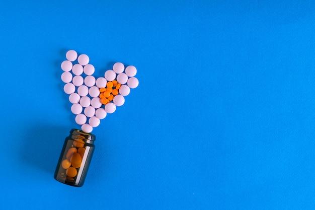Les comprimés sont versés à partir d'une bulle sous la forme d'un cœur de deux couleurs.